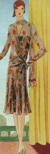 1920's fashion. Ruth Wade. Rust dress and hat beside yellow curtain w